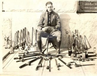 Police officer poses with opium paraphernalia after opium den raids